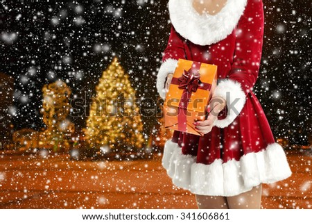 blurred background of winter night and big gift and red dress  - stock photo