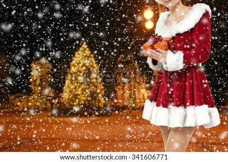 blurred background of winter night and golden box in hands  - stock photo