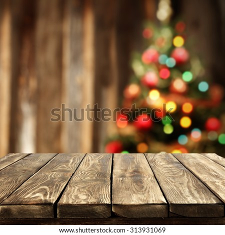 blurred background of xmas tree lights and wall with table of brown color  - stock photo