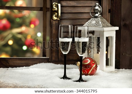 blurred background of xmas tree lights and window of red ball and glasses  - stock photo