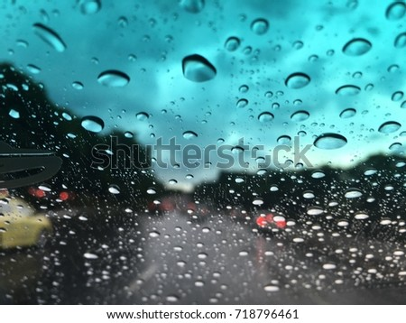 Blurred background, Raindrops on the windshield, street lights at evening on a rainy day.