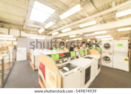 Blurred Background Retail Store With Rows Of Home Appliances Equipments.  Defocused Washing Machines, Electric
