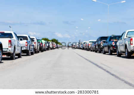 blurred background row of parked cars in parking lot - stock photo