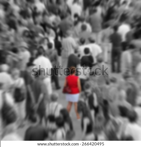 Blurred background showing woman in red in a middle of a crowd in black and white. - stock photo