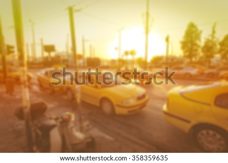Blurred background: street with road, cars, pedestrian, crosswalk, traffic lights, signs etc on the sunset with beautiful sun rays in Athens greece Image with toning - stock photo