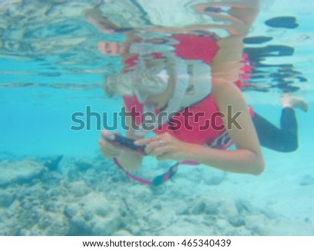 Blurred Background the women snorkeling and take a photo of corals reef in maldives