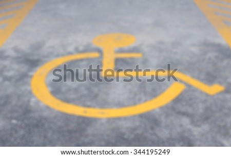 Blurred background wheel chair symbol in parking lot - stock photo