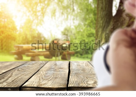 blurred background with young woman and dark brown wooden table  - stock photo