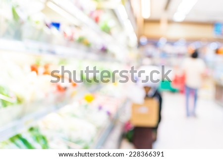 Blurred background : Woman officer put in order of Fresh vegetable into product shelf  - stock photo