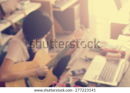 Blurred background : woman play guitar in workspace with vintage filter - stock photo