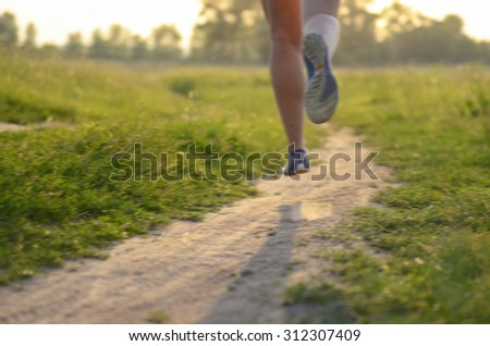 Blurred background: woman runner running on rural road on sunset or sunrise, sport and fitness concept  - stock photo