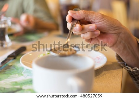 Blurred background woman's hand with the spoon while eating soup in the restaurant