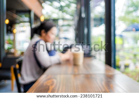Blurred background : woman sitting at coffee shop with ice coffee on wooden table and see through shop window - stock photo