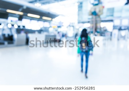 Blurred background : Woman traveler walk in to terminal at airport terminal departure blur background with bokeh light - stock photo