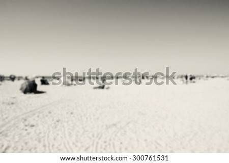 Blurred beach photo. People relaxing on beach. Vacation background (Trouville-sur-Mer, Normandy, France) Aged photo. Black and white. - stock photo