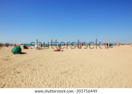 Blurred beach photo. People relaxing on beach. Vacation background (Trouville-sur-Mer, Normandy, France) - stock photo
