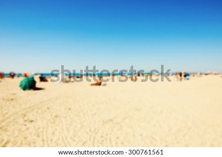 Blurred beach photo. People relaxing on beach. Vivid sunlight. Vacation background (Trouville-sur-Mer, Normandy, France) - stock photo