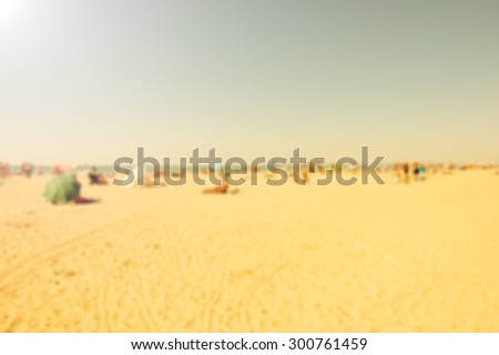 Blurred beach photo. Sun beams glow. People relaxing on beach. Vacation background (Trouville-sur-Mer, Normandy, France) Retro aged photo.  - stock photo