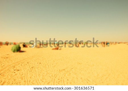 Blurred beach photo with selective focus on the sand at foreground. People relaxing on beach. Vacation background (Trouville-sur-Mer, Normandy, France) Retro aged photo.  - stock photo