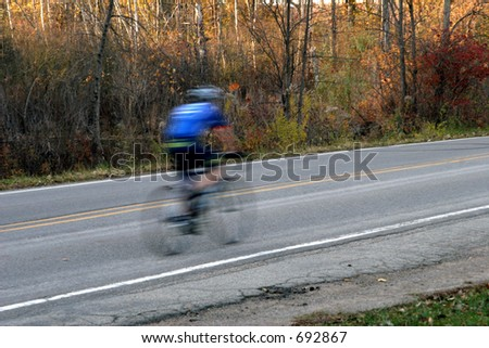 Blurred bicyclist riding along roadway