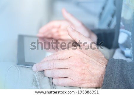 blurred blue toned close up view of man working with tablet - stock photo