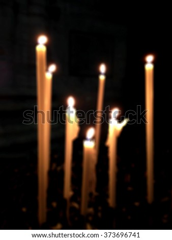 blurred blurry soft unfocused a lot of burning candles in church, cathedral Duomo  - stock photo