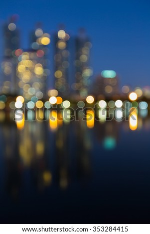 Blurred bokeh light city office building with water reflection at night - stock photo