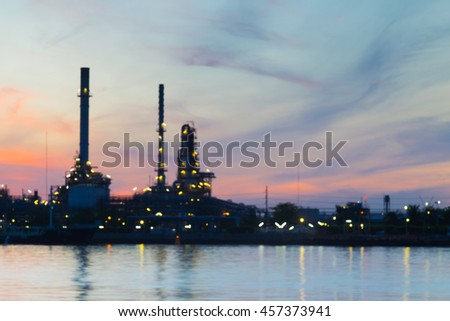 Blurred bokeh oil refinery riverfront with beautiful sunrise sky baclground