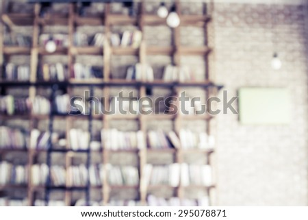 Blurred books on the shelf with brick wall in public library in vintage color tone - stock photo