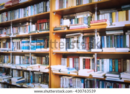 blurred bookshelf in library for your background design - stock photo