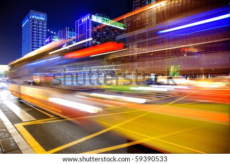 blurred bus light trails in downtown night-scape - stock photo