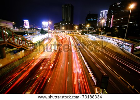 blurred bus light trails in downtown night-scape in hongkong. - stock photo