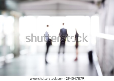 Blurred business people standing in building hall , can be used as abstract background - stock photo
