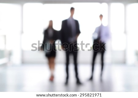 Blurred business people standing in building hall , can be used as background - stock photo