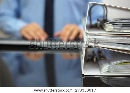 blurred businessman is typing on computer keyboard with documentation in focus - stock photo