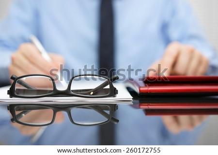 blurred businessman is working in office , focus is on eyeglasses - stock photo