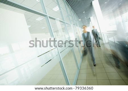 Blurred businesspeople moving in the corridor - stock photo