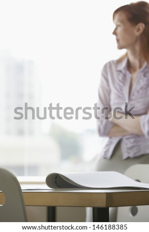 Blurred businesswoman looking out of window with focus on documents on desk in foreground - stock photo