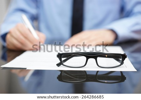 Blurred busy entrepreneur in background with focus on glasses - stock photo