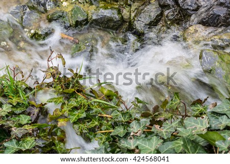 Blurred by water spray Small waterfall, cascade flowing over mossy boulders in a botanical garden. - stock photo