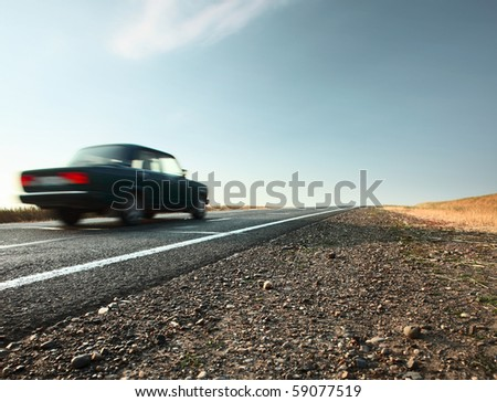 Blurred car on an asphalt road and blue sky with clouds - stock photo