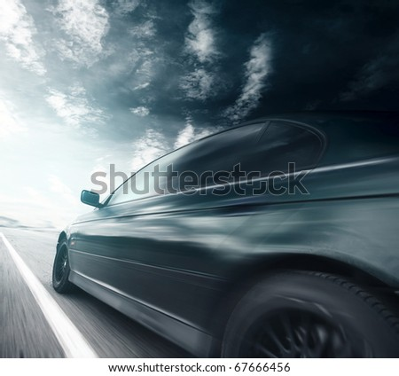 Blurred car on asphalt road and sky with clouds - stock photo
