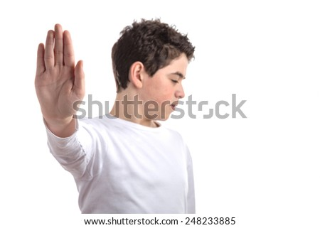 Blurred Caucasian smooth-skinned teen in a white long sleeve t-shirt smiles making Talk to the hand gesture with right hand - stock photo