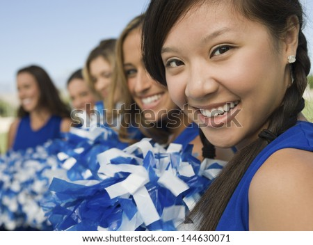 Blurred cheerleaders in a row with focus on girl in foreground - stock photo