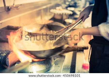 blurred chef of a restaurant kitchen, motion cooking, take photo low speed - stock photo