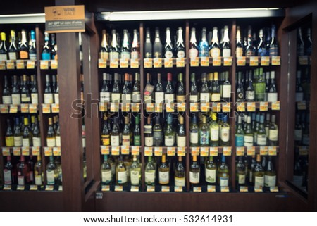 Blurred chilled wine section in the massive double wine aisle at store in  Texas, US. Defocused rows of Wine Liquor bottle supermarket wooden shelf. Alcoholic beverage background. Vintage tone