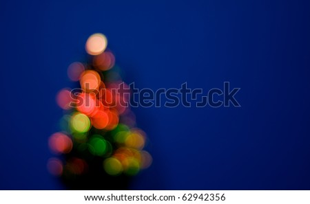 Blurred christmas tree on blue background - stock photo