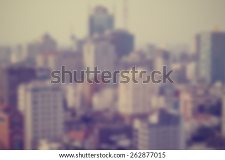 Blurred city background suitable as a background for text. Designed to work with most text colors including white. Artistic intent with filters and desaturation.  High rise buildings - stock photo