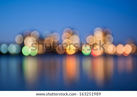 Blurred city lights with bokeh effect reflected on water - stock photo