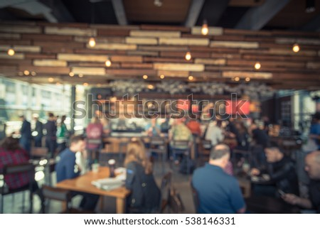 Blurred coffee shop or cafe restaurant in sunny fall morning at Dallas, Texas, US. Blur people, customer waiting for order, pickup and enjoy coffe in bar counter, tables in coffee shop. Vintage tone